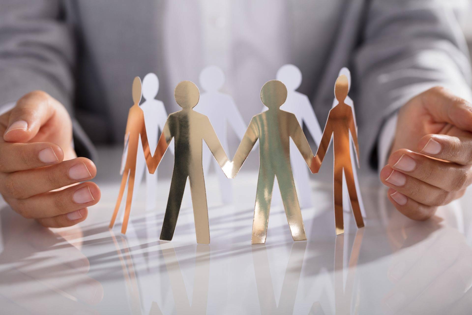 csoportkép papirbábukból, óvó, támogató kezekkel